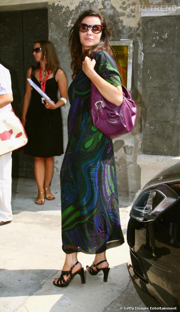 Dans les rues de Venise, Emmanuelle Béart s'offre une robe aux imprimés psychédéliques, très hippie. Lunette  papillon  sur le nez et sandales à talons, la star s'est concoctée un look baba cool et glamour, à son image.