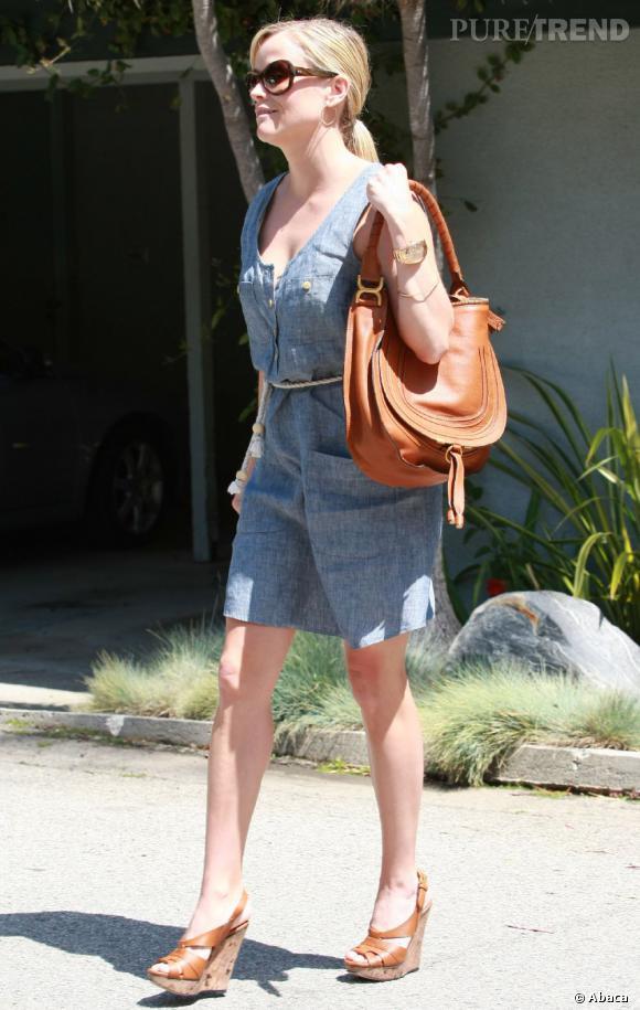Reese Witherspoon est désomais une source d'inspiration pour les fashionistas. Robe en jean, sac Chloé et compensées aux pieds, elle s'offre un summer look féminin et trendy.