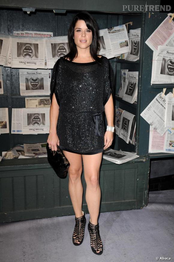 Neve Campbell porte une robe glitter noire. Une pièce classique mais efficace. On regrette les sandales cage, définitivement peu sexy.