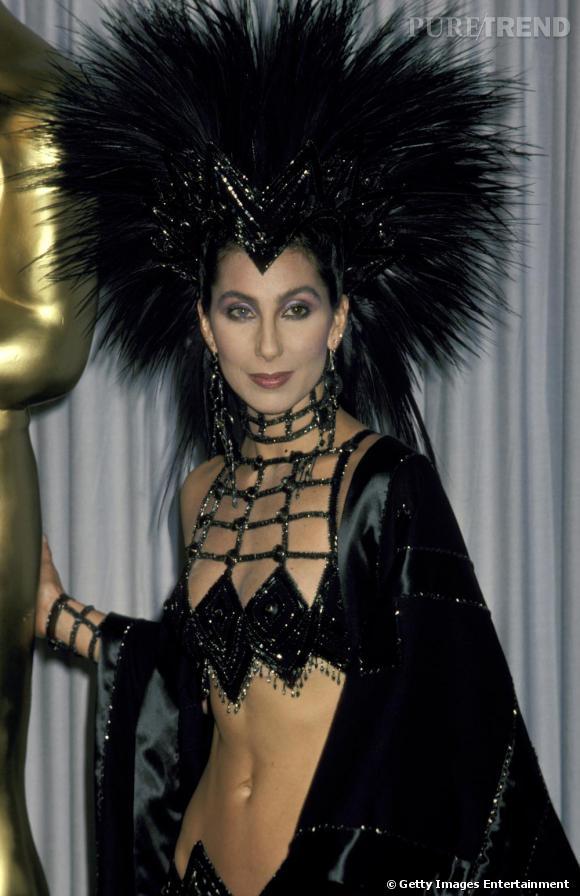 Entre reine gothique et créature disco, il n'y a qu'un pas ou plutôt, une robe Bob Mackie. Cher porte à nouveau les créations spectaculaires du couturier lors des Oscars de 1986.