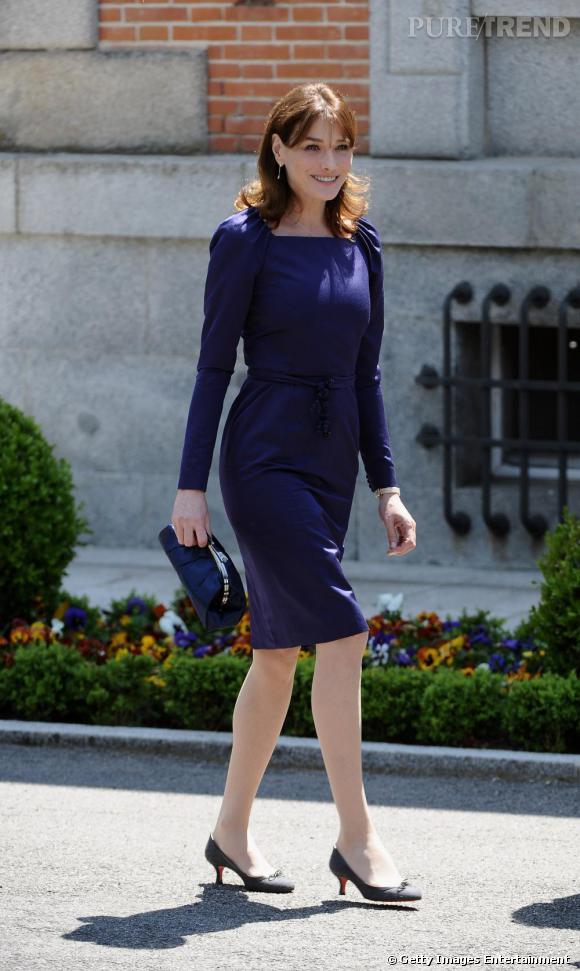 Pochette bouffante au fermoir rétro Chanel, Carla Bruni succombe à l'élégance du bleu nuit satiné.