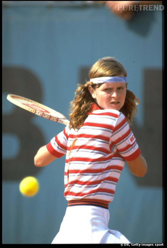 Hanna Mandlikova essaie de lui voler la vedette avec ce polo rayé et une coiffure bandeau très réussie. On notera que dans la mode tennis, il est crucial d'assortir tous les éléments de sa tenue sans aucun second degré.