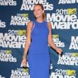 L'actrice porte une robe Michael Kors bleu éléctrique qui lui arrive aux genoux.
