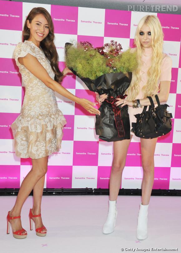 Taylor, accompagnée du mannequin Japonais Jessica Michibata, en robe nude et talons rouges.
