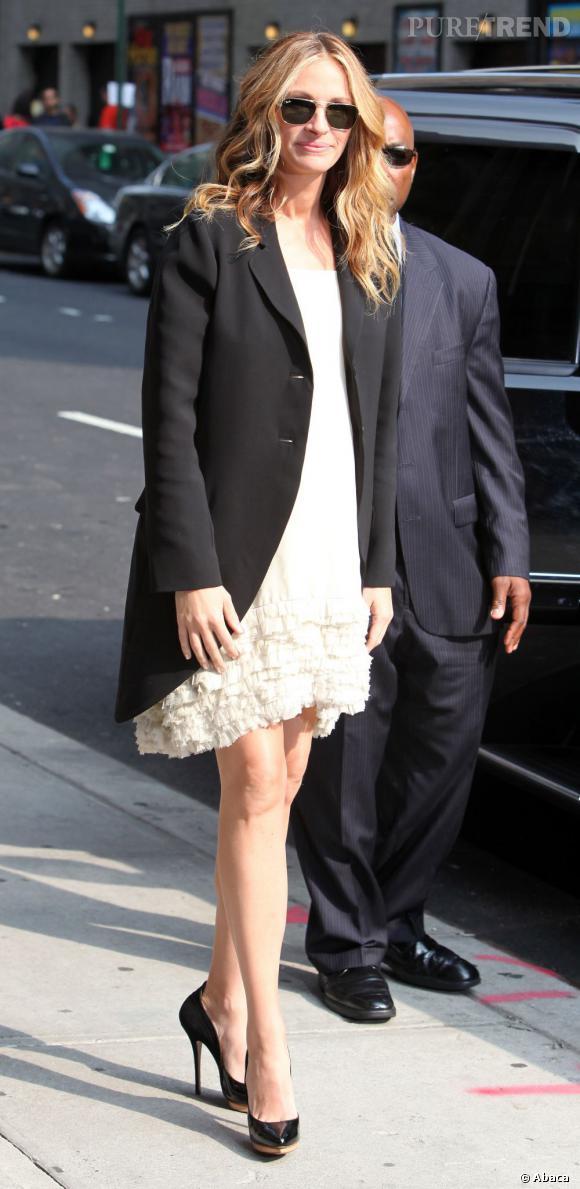 Julia porte une jolie robe blanche qui flatte son teint hâlé.