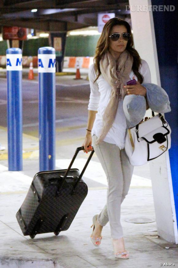 Eva Longoria, sexy et douée avec une valise à roulettes Vuitton et en sac cartable en bandoulière. La perfection ?