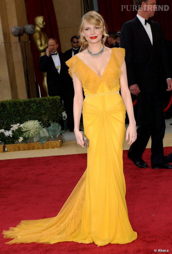 Rétro, Michelle Williams prend la pose dans une robe moutarde drapée et parsemée de volants sur le décolleté.