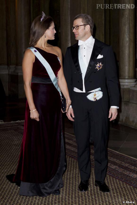 La jeune femme sort le grand jeu avec une robe en velours bordeaux one shoulder qui flatte parfaitement ses courbes.