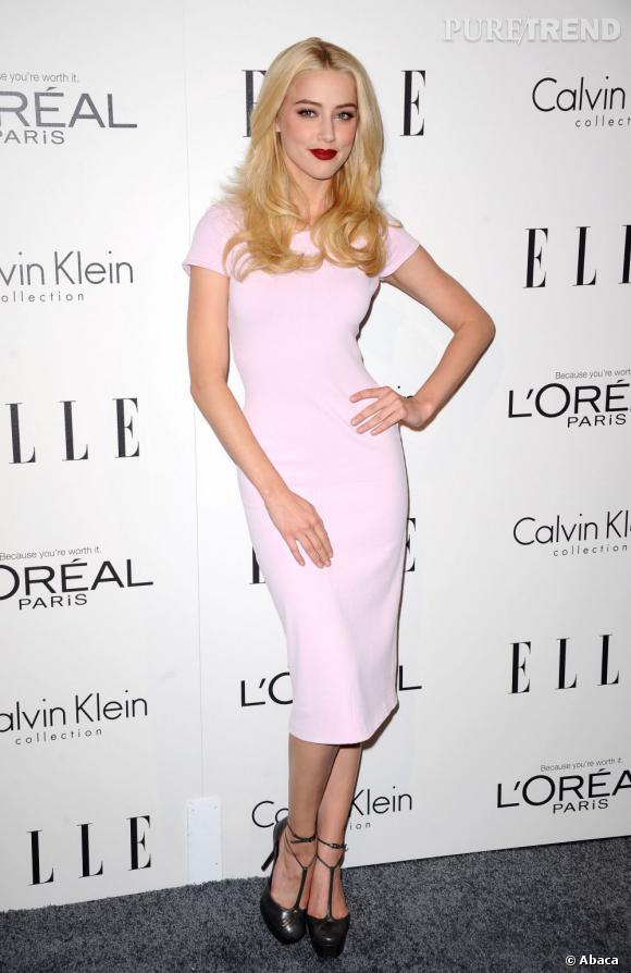 Amber Heard choisit une robe Calvin Klein rose pastel. Avec sa bouche rouge, elle fait femme fatale.