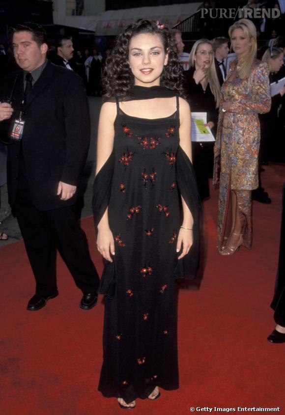 Le flop 1ère apparition : Pauvre Mila Kunis, personne ne semble échapper aux faux pas dans les années 90. En 1999, l'actrice a 16 ans. Dans une longue robe informe elle cache sa silhouette et se maquille un peu trop généreusement.