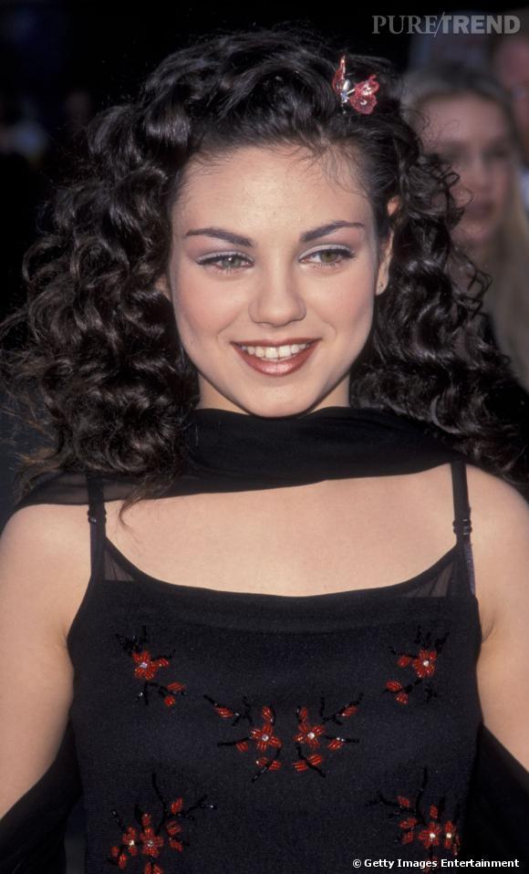 1999 : Mila Kunis a 16 ans et encore tout à apprendre. De la crinière frisée accessoirisée avec une barrette papillon au fard beige et au rouge à lèvres brillant sur les lèvres, tout fleure bon les errements de l'adolescence.