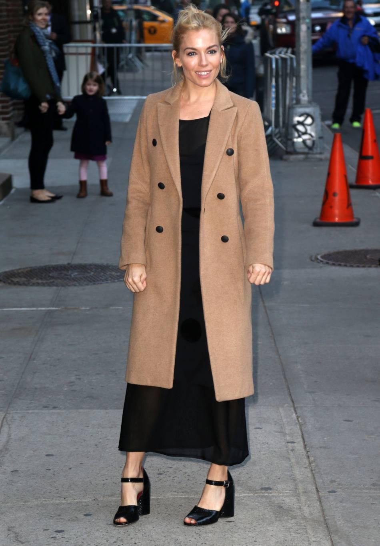 """Sienna Miller à la conquête des USA, arrivant au """"Late Show"""" dans une robe noire et un manteau camel très chic. Quel mix !"""