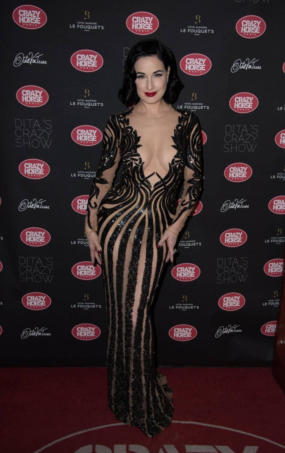 Dita Von Teese porte une longue robe transparente et séduit sur le tapis rouge.
