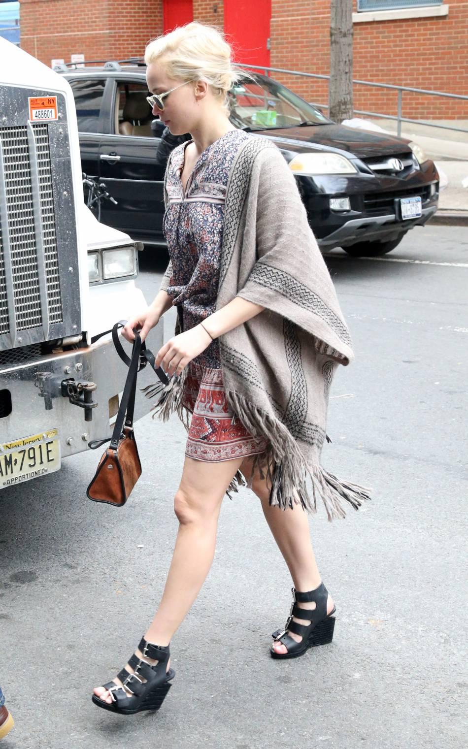 Jennifer Lawrence sort le gilet poncho à frange pour se couvrir un peu. Sa robe est très estivale.