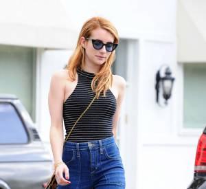 Emma Roberts porte un jean flare accompagné d'un crop top moulant et d'une paire de sandales à talons rouges flashy.
