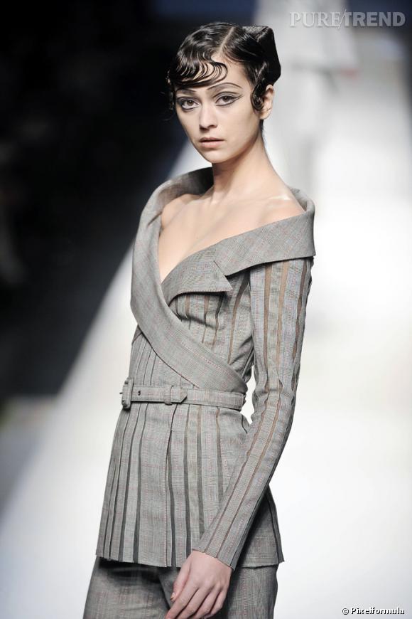 Tiré de la collection de haute couture printemps-été 2009 signée [brand=1379]Jean Paul Gaultier[/brand] , cet ensemble démontre plusieurs qualités. Regardons l'allure, les cheveux. Pas de doute, c'est une garçonne... pourtant féminisée à l'extrême. Quoi de plus masculin qu'un costume croisé Prince-de Galles ?