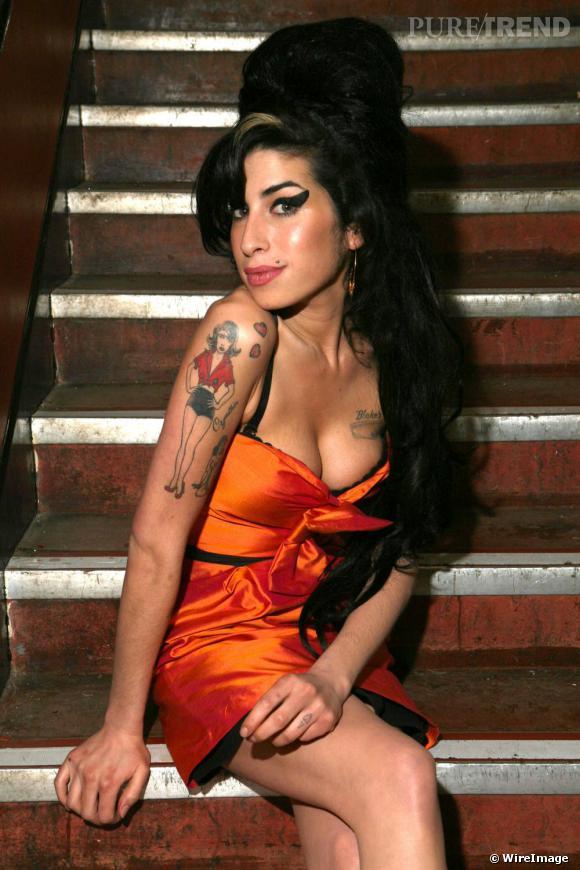 """Amy Winehouse, la Betty Page des pub. Cette version très rock'n'roll des nymphettes de Gil Elvgren, allie avec désinvolture allure de pin up et attitude de marin. Amy Winehouse et son mythique album """"back to black"""" inscrit son style et sa musique dans les mémoires collectives. Voix rauque et ennivrante, coiffure digne d'une poupée espagnole posée sur un meuble Hifi, la diva soul s'impose comme une icône mode du xxième siècle.    Caractéristiques de la coupe de cheveux :    La coiffure d'Amy a inspiré plus d'un. Le kaiser lui même s'est inspiré de la célèbre choucroute de la chanteuse pour le défilé Dior printemps-été 2008.   Pour se concocter un crépage à la Winehouse, on n'hésite pas à abuser des artifices. On se procure un boudin pour donner du volume à son chignon."""