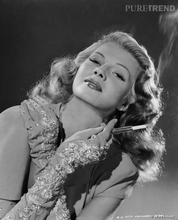 """Chevelure sensuellement ondulée, rouge carmin au lèvres: cette diva hollywoodienne est incontestablement une icône coiffure. Rita Hayworth ,de son vrai nom Margarita Carmen Cansino, reste le sex symbol des années 40. Surnommée la """"déesse de l'amour"""", elle devient une légende dans le rôle de Gilda.    La coiffure ?    On dispose des gros rouleaux sur l'ensemble de sa chevelure. On laisse pauser 1 heure. On déroule délicatement les bigoudis et brosse lègèrement les ondulations.    Pourquoi on aime :    Une coiffure certes rétro, qui donne une véritable touche de femme fatale.    Qui l'a adopté :  Scarlett Johanson, Miranda Kerr"""