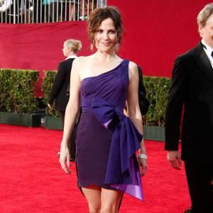 La brunette mise sur une robe asymétrique et bicolore. La taille étranglée par un large noeud, elle ajoute la touche girly à la pièce épurée. La bonne idée ? Choisir une couleur qui réchaffe les teints pâles.