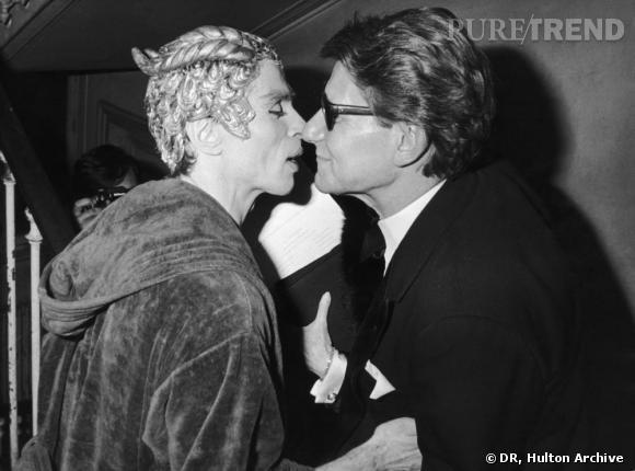 K comme Kouros       Pour le lancement en 1981 de son nouveau parfum pour homme, Kouros, Yves Saint Laurent fait danser Noureev à l'Opéra Comique devant 1200 personnes. Une manière de célébrer les Arts, plus précisemment le ballet, et l'univers du créateur qui a longtemps créé des costumes de scènes. Noureev, Yves Saint Laurent et Pierre Bergé se sont rencontrés pour la première fois en 1961.