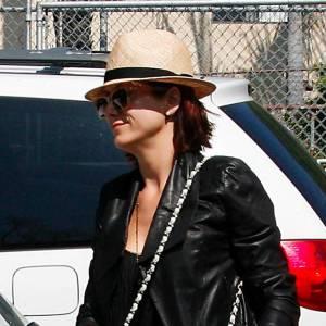 Kate Walsh fait confiance aux classiques : sac matelassé Chanel et chapeau de paille style borsalino avec un ruban noir.