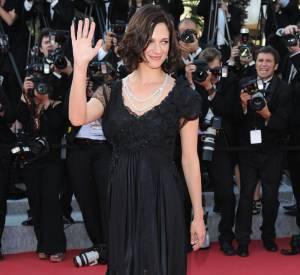 Une souriante Asia Argento, poétique en robe noire longue et fluide.