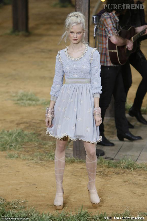 Défilé Chanel Printemps-Eté 2010    Une robe dans un ton bleu qui rappelle l'enfance. Le pastel se marie toujours très bien au tissu légèrement froissé et aux liserés fleuris.
