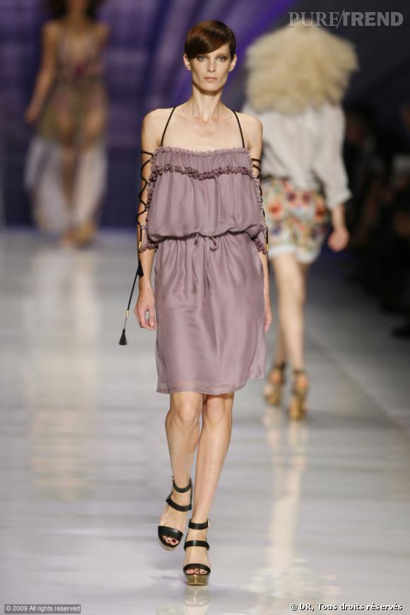 Défilé Etro Printemps-Eté 2010    Du parme sur une robe légère et bordée de pompons. Un air de muse antique avec les lacets qui ceignent les bras qui donnent au final un look féminin et audacieux.