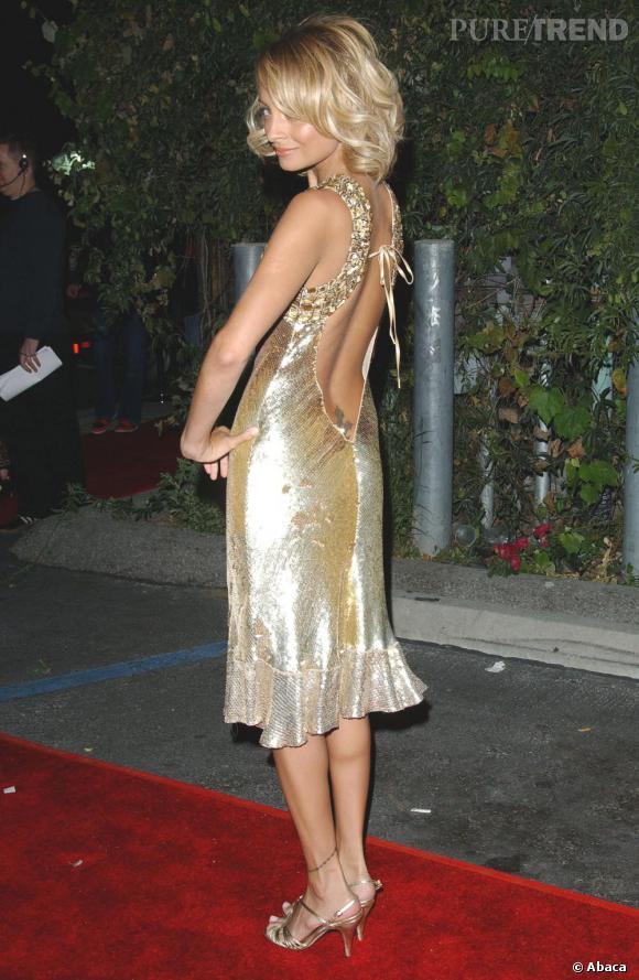 Une petite robe dorée ne fait pas tout. Nicole Richie affiche un sourire en coin, la regard coquin sous une mèche rebelle pour une touche de mystère, et enfin, une découpe qui laisse peu de place à l'imagination.
