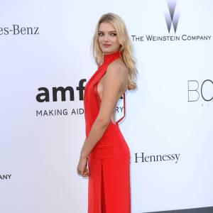 Lily Donaldson maîtrise la pose de profil en robe rouge séduction.