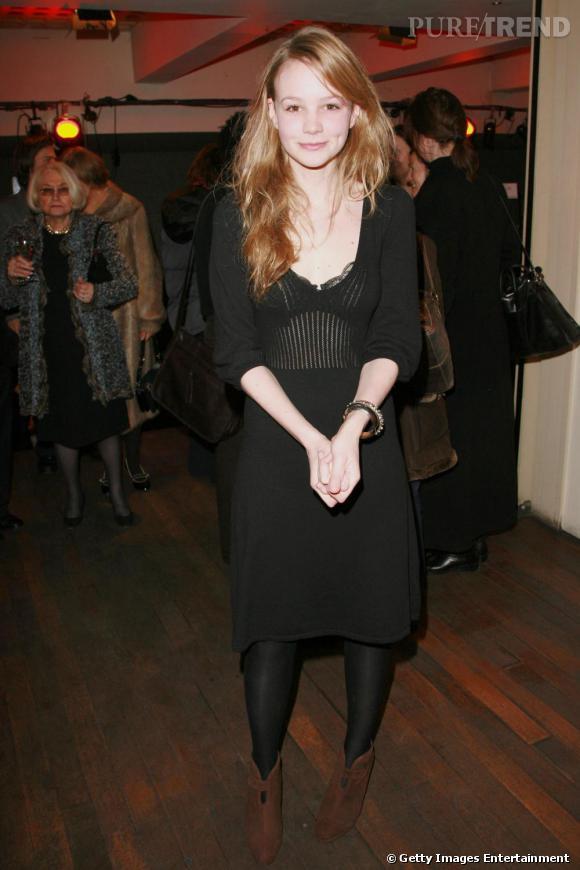 Carey Mulligan en 2007 : les cheveux longs et blonds encadrent son visage enfantin. Timide, elle opte pour une petite robe noire et des bottines marrons.