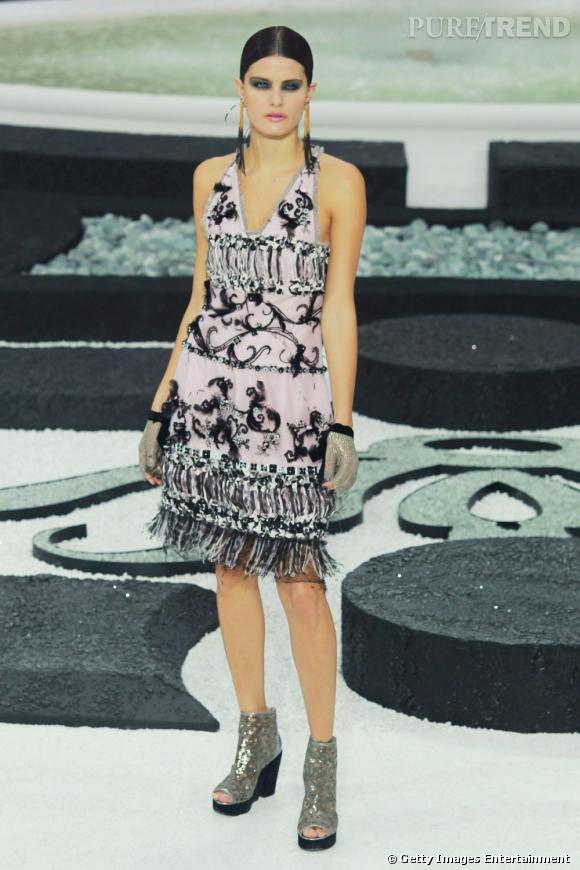 Aussi belle en maillot de bain qu'en tenue Haute Couture. Ici, vêtue d'une robe Chanel brodée et de chaussures compensées à paillettes.