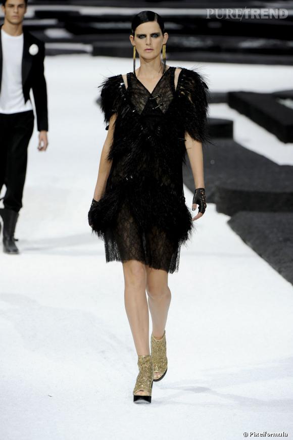 Défilé Chanel printemps-été 2010, la même robe, mais portée par Stella Tennant, avec des mitaines en cuir clouté et des boots dorées.