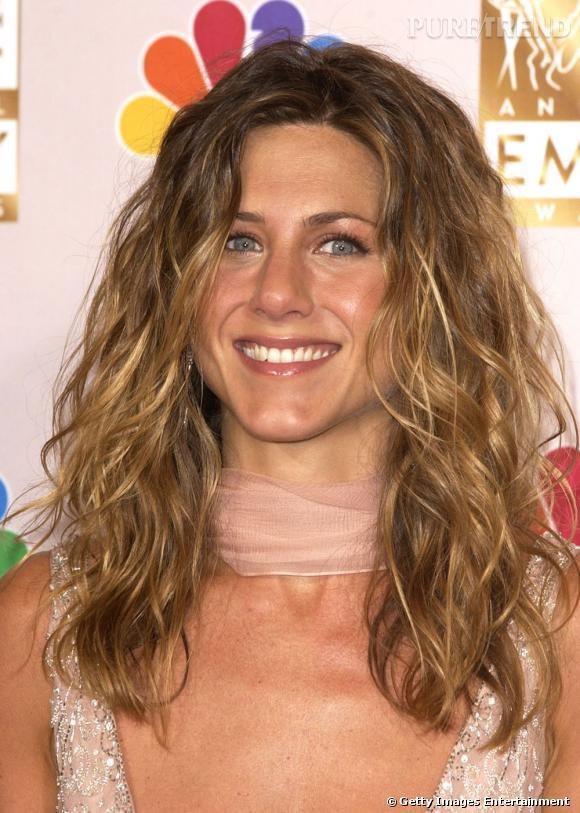 """Alors à l'époque de """"Friends"""",  Jennifer Aniston  s'est laissée tenter par une coupe de cheveux bouclés et longs, façon wavy estival. Une coiffure à porter aussi bien pour une soirée qu'à la plage."""