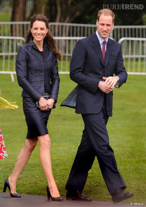 Kate Middleton opte pour un tailleur classique mais pourtant très moderne, grâce à son tissu satiné à la coupe près du corps.