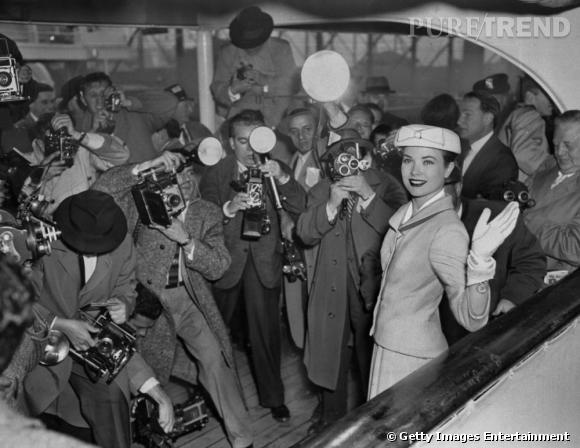 Grace Kelly pose dans un tailleur jupe devant une horde de photographes. Elle accessoirise sa tenue d'une paire de gants claire et d'un petit chapeau rond.