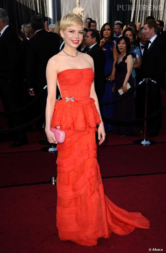 Michelle Williams tire son épingle du jeu dans une robe Louis Vuitton rouge orangée à la finition nude donnant l'impression d'un dos nu.