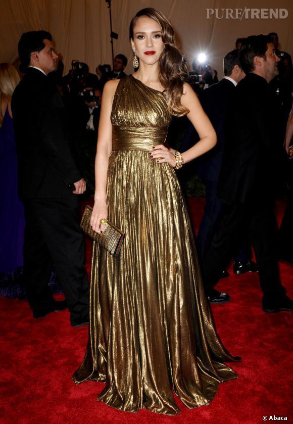 Jessica Alba assume le total look dorée en y ajoutant une minaudière Roger Vivier.