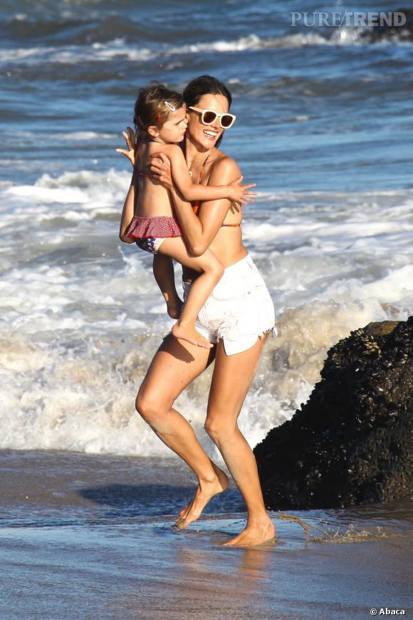 Pour effleurer les vagues des pieds avec sa fille Anja, Alessandra opte pour un maillot de bain façon coucher de soleil et un short blanc