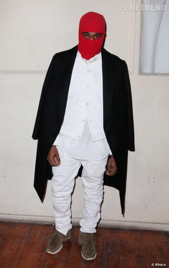 Kanye West a choisi une tenue immaculée et un long manteau noir pour le défilé Maison Martin Margiela Haute-Couture .