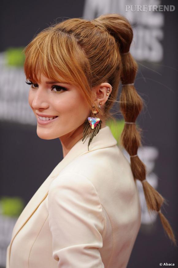 Bella Thorne met l'accent sur ses yeux avec une frange de cils parfaite encadrée d'une frange. Elle personnalise sa ponytail avec des élastiques tout le long.