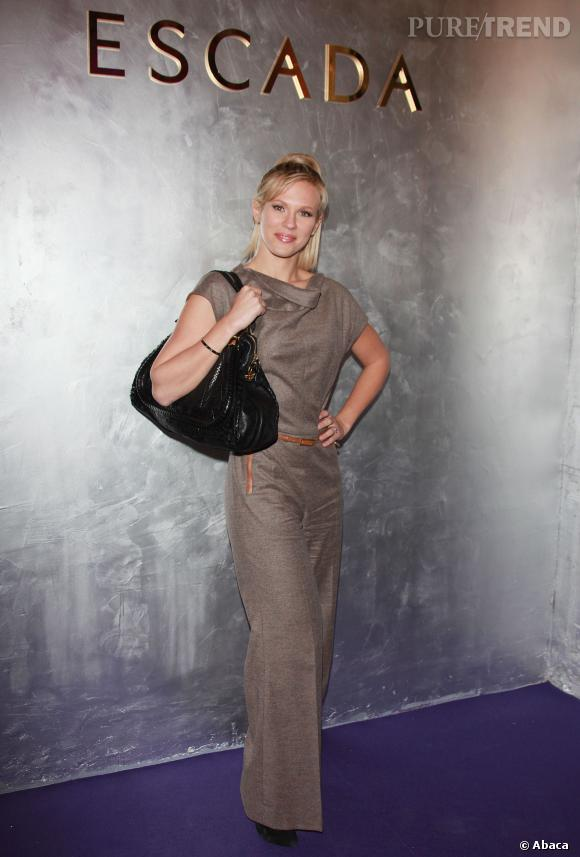 Chez Escada, Lorie mise sur une robe longue taupe et des extensions blondes.