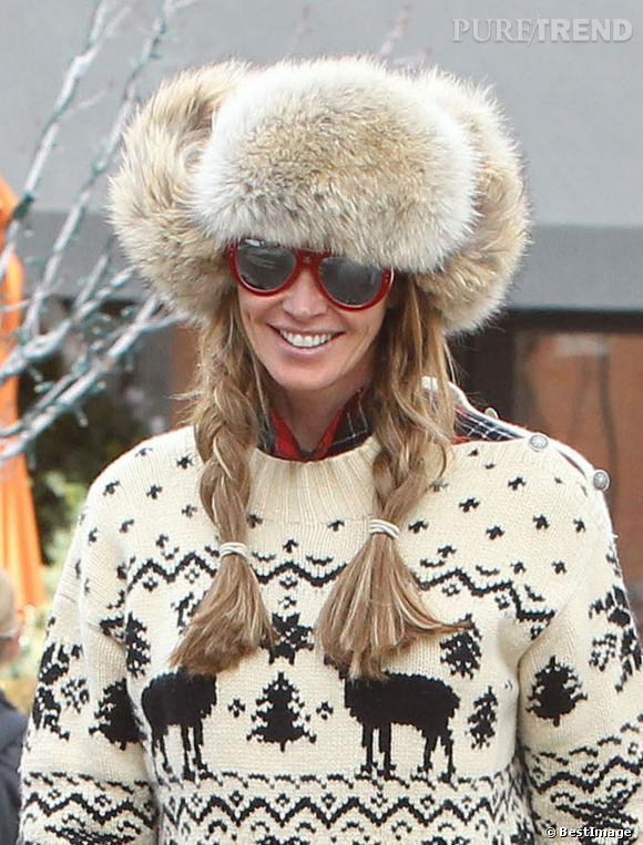Elle Macpherson réchauffe son teint avec des lunettes de soleil rouges.