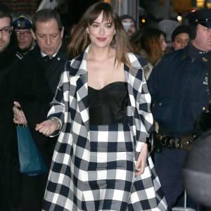 """Dakota Johnson en bustier noir et jupe crayon à gros carreaux noirs et blancs lors de son apparition sur le plateau de """"The Late Show"""", ce mardi 17 février 2015."""