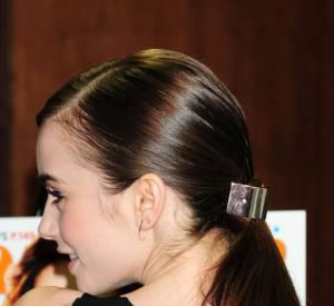 La bonne astuce de Lily Collins pour une coiffure chic rapide et facile : une barette dorée qui cache l'attache de sa queue de cheval.