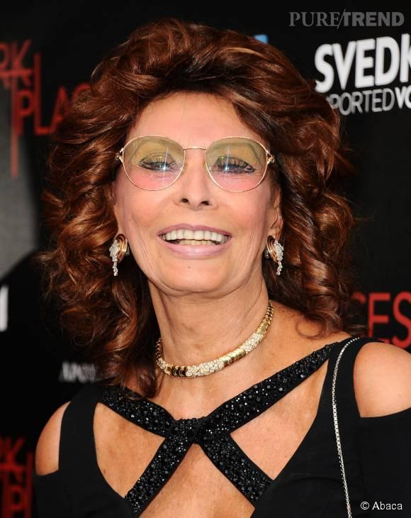 Sophia Loren porte des bijoux dorés et des lunettes aux verres colorés. Rien ne l'arrête.