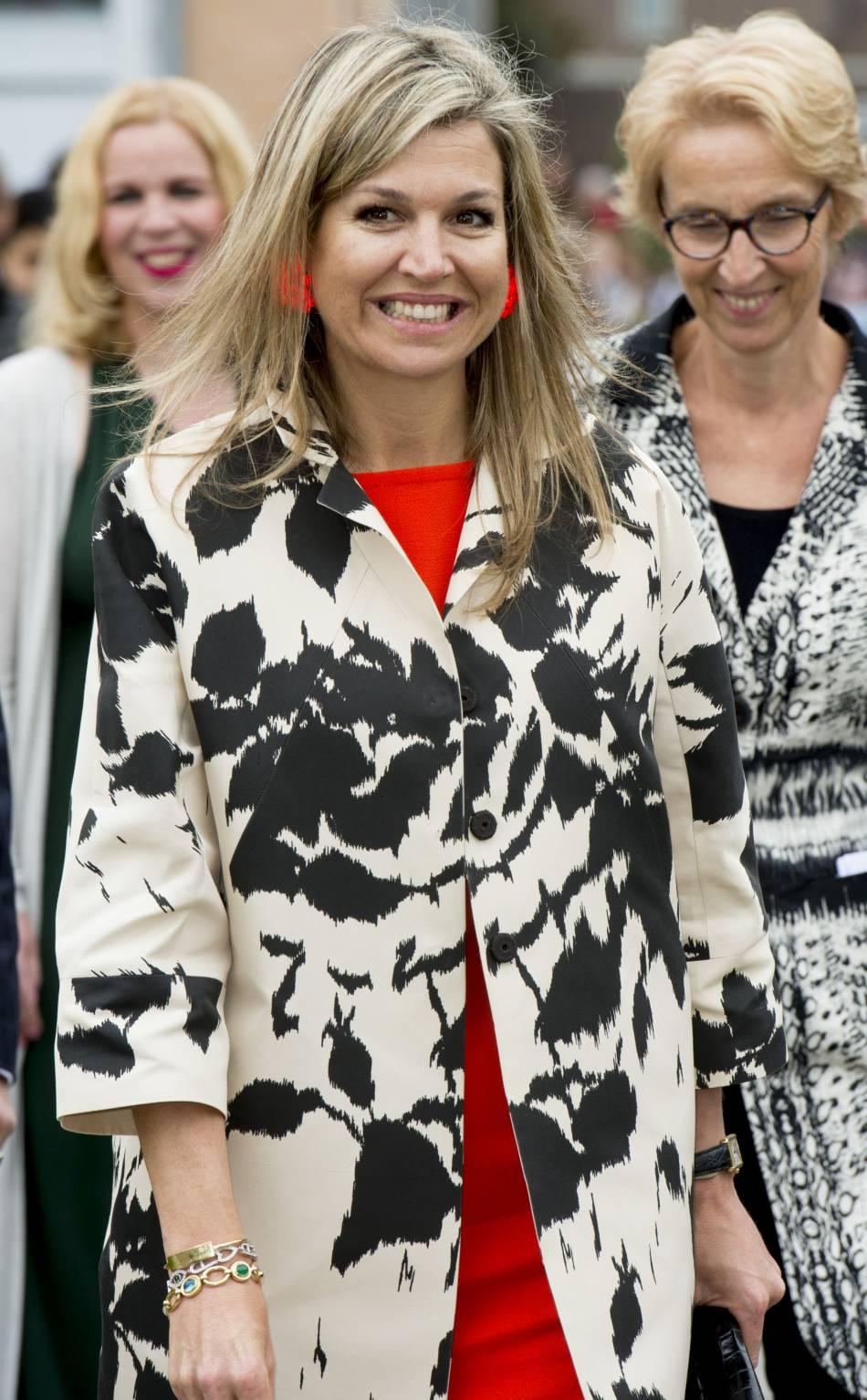 La reine a associé un manteau à imprimés à une robe vermillon.