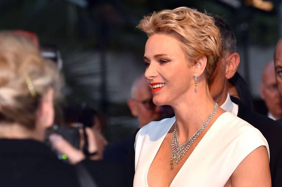 La princesse Charlène de Monaco souriante, glamour et même sexy dans une robe blanche décolletée.