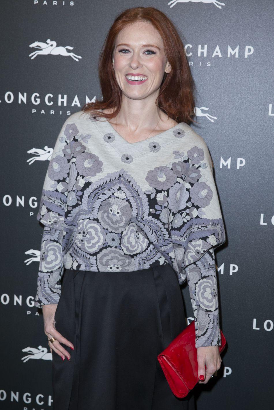 Audrey Fleurot était à l'ouverture de la boutique Longchamps. Pull à gros motifs noirs et blancs, jupe noire et la touche de couleur assortie à sa chevelure flamboyante : une pochette rouge.