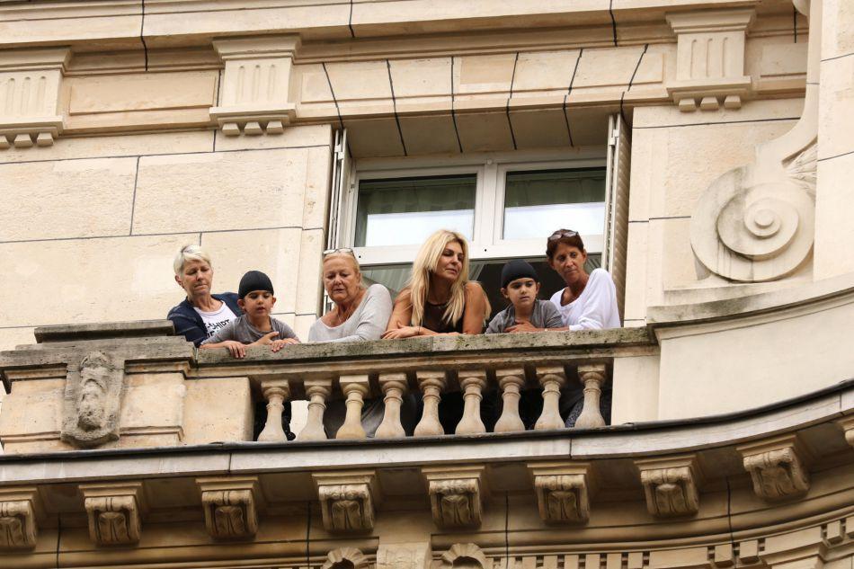 Ses jumeaux, Nelson et Eddy, suivent la sortie de leur maman d'un air amusé depuis leur balcon.